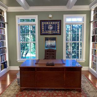 Klassisk inredning av ett mellanstort arbetsrum, med ett bibliotek, gröna väggar, mellanmörkt trägolv, ett fristående skrivbord och orange golv