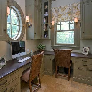 Inspiration för ett mellanstort vintage hemmabibliotek, med ett inbyggt skrivbord, beige väggar, kalkstensgolv och brunt golv