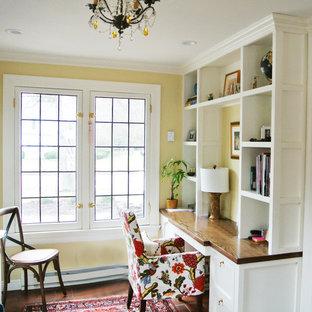 Idee per uno studio chic di medie dimensioni con libreria, pareti gialle, pavimento in terracotta, nessun camino, scrivania incassata e pavimento rosso