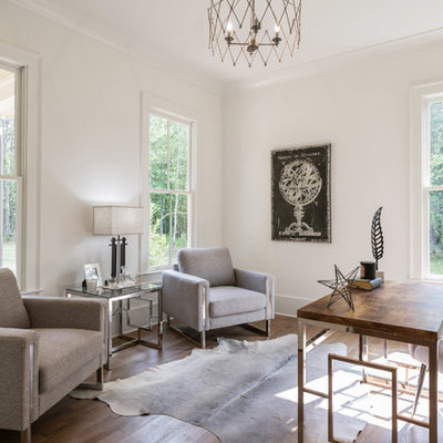 Country freestanding desk medium tone wood floor and brown floor home office photo in Atlanta with white walls