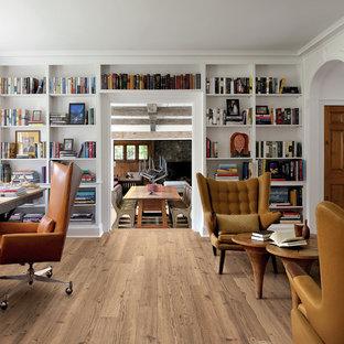 Immagine di uno studio chic con pareti bianche, parquet chiaro, camino classico, scrivania autoportante, libreria e cornice del camino in pietra