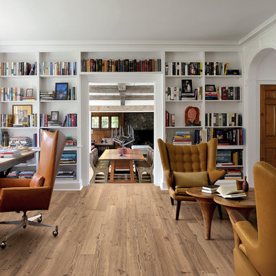 Transitional freestanding desk light wood floor home office library photo in London with white walls, a standard fireplace and a stone fireplace
