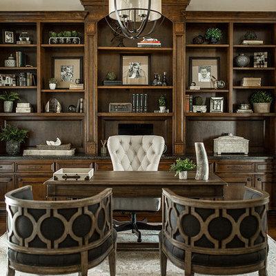 Example of a classic freestanding desk dark wood floor and brown floor study room design in Houston with beige walls