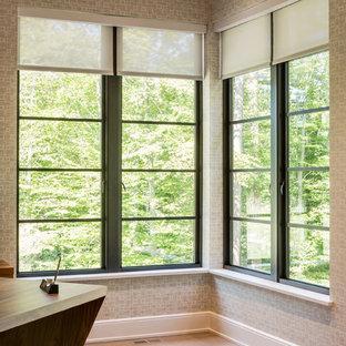 フィラデルフィアの中くらいのトランジショナルスタイルのおしゃれな書斎 (グレーの壁、淡色無垢フローリング、両方向型暖炉、コンクリートの暖炉まわり、自立型机、ベージュの床) の写真