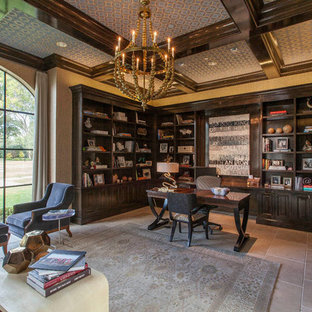 This is an example of a mediterranean study in Dallas with beige walls, limestone flooring and a freestanding desk.