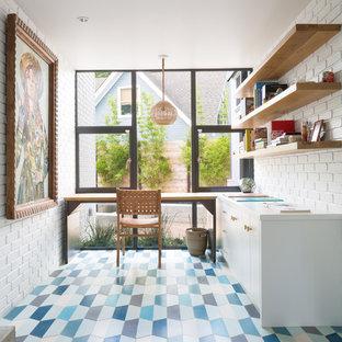 Immagine di uno studio minimalista di medie dimensioni con pareti bianche, scrivania autoportante e pavimento blu