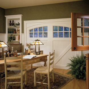 Inredning av ett klassiskt arbetsrum, med gröna väggar, mellanmörkt trägolv och ett fristående skrivbord