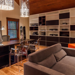 Inspiration for a large modern home studio in Salt Lake City with white walls, medium hardwood flooring, a freestanding desk, a standard fireplace, a metal fireplace surround and brown floors.