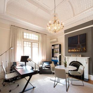 Ispirazione per un ufficio tradizionale di medie dimensioni con pareti beige, pavimento in legno massello medio, camino classico, cornice del camino in intonaco e scrivania autoportante