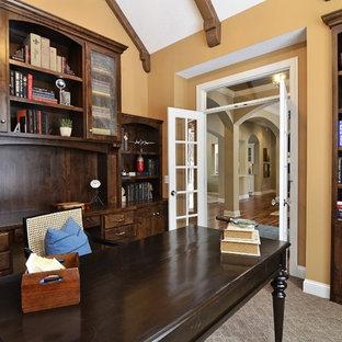Imagen de despacho clásico con paredes amarillas, moqueta y escritorio independiente