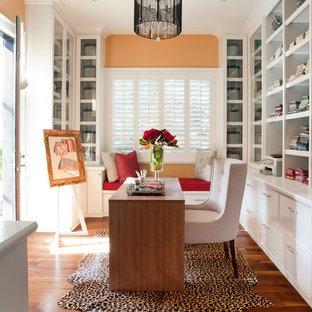 На фото: рабочее место среднего размера в современном стиле с оранжевыми стенами, темным паркетным полом, отдельно стоящим рабочим столом и коричневым полом без камина с