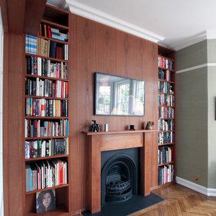 ロンドンの巨大なミッドセンチュリースタイルのおしゃれな書斎 (標準型暖炉、木材の暖炉まわり、緑の壁、無垢フローリング、自立型机) の写真