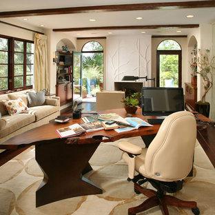 ロサンゼルスの大きいトランジショナルスタイルのおしゃれな書斎 (濃色無垢フローリング、自立型机、ベージュの壁、標準型暖炉、漆喰の暖炉まわり、茶色い床) の写真