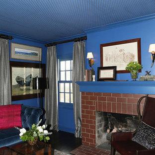 Immagine di uno studio classico di medie dimensioni con libreria, pareti blu, pavimento in legno massello medio, camino classico, cornice del camino in mattoni, scrivania autoportante e pavimento marrone