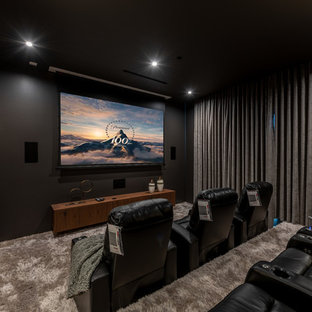 Home theater - contemporary enclosed carpeted and gray floor home theater idea in Los Angeles with black walls and a projector screen