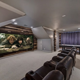 Mid-sized mountain style enclosed carpeted and beige floor home theater photo in Charlotte with gray walls and a projector screen
