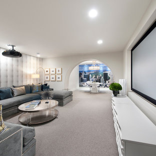 Transitional home theatre in Minneapolis with white walls, carpet, a projector screen and grey floor.