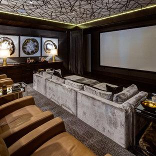 Idées déco pour une très grande salle de cinéma classique fermée avec moquette, un écran de projection, un mur marron et un sol multicolore.