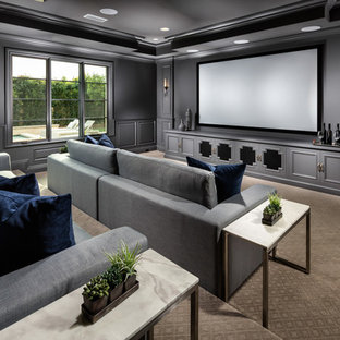 Traditional enclosed home theatre in Los Angeles with grey walls, carpet, a projector screen and beige floor.