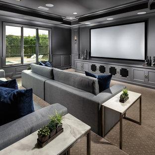 ロサンゼルスのトラディショナルスタイルのおしゃれな独立型シアタールーム (グレーの壁、カーペット敷き、プロジェクタースクリーン、ベージュの床) の写真