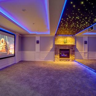 Réalisation d'une grand salle de cinéma minimaliste ouverte avec un mur gris, moquette et un écran de projection.