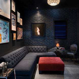 Ejemplo de cine en casa cerrado, contemporáneo, con paredes negras, suelo de cemento, suelo gris y televisor colgado en la pared