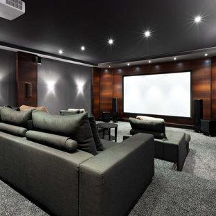Foto di un ampio home theatre moderno chiuso con pareti grigie, moquette, schermo di proiezione e pavimento grigio