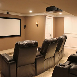 Immagine di un home theatre classico di medie dimensioni e chiuso con pareti marroni, moquette, schermo di proiezione e pavimento beige
