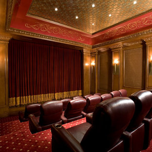 Photo of an expansive mediterranean enclosed home cinema in Las Vegas with carpet, a projector screen and red floors.