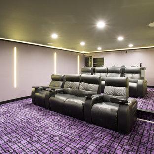 Пример оригинального дизайна: большой изолированный домашний кинотеатр в стиле модернизм с фиолетовыми стенами, ковровым покрытием, проектором и фиолетовым полом