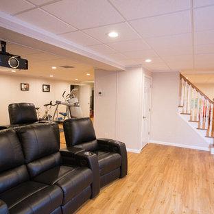 Inredning av ett modernt stort öppen hemmabio, med beige väggar, ljust trägolv, beiget golv och projektorduk