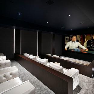 Diseño de cine en casa abierto, actual, extra grande, con paredes negras, moqueta, pantalla de proyección y suelo gris