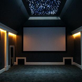 Immagine di un home theatre minimalista di medie dimensioni e chiuso con pareti grigie, moquette e schermo di proiezione