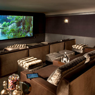 This is an example of a large traditional enclosed home theatre in San Diego with purple walls, carpet, a projector screen and brown floor.