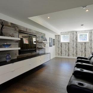 Imagen de cine en casa cerrado, contemporáneo, grande, con paredes blancas, suelo de madera oscura y pared multimedia