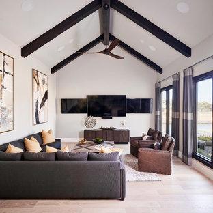 Ejemplo de cine en casa clásico renovado con paredes blancas, suelo de madera clara y televisor colgado en la pared