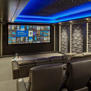 This is an example of a large classic enclosed home cinema in Boston with grey walls, carpet, a projector screen and grey floors.