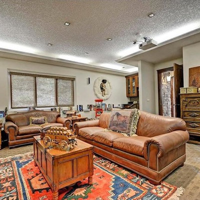 Inspiration for a large southwestern enclosed carpeted and beige floor home theater remodel with white walls and a projector screen