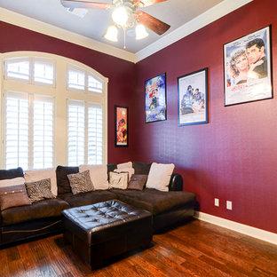 Réalisation d'une salle de cinéma victorienne de taille moyenne avec un mur rouge, un sol en bois foncé et un téléviseur fixé au mur.