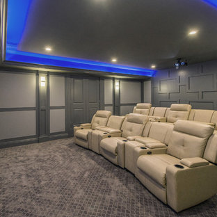 Elegant enclosed carpeted and gray floor home theater photo in New York with gray walls and a projector screen