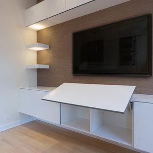 Großes, Offenes Modernes Heimkino mit weißer Wandfarbe, hellem Holzboden und Wand-TV in Chicago