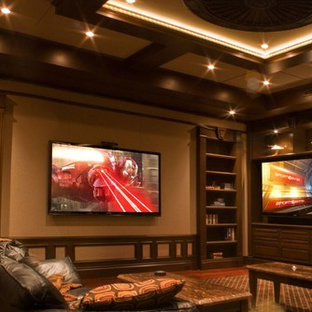Large elegant open concept medium tone wood floor and brown floor home theater photo in Miami with beige walls and a wall-mounted tv