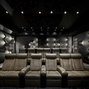 Immagine di un grande home theatre design chiuso con pareti grigie, moquette, schermo di proiezione e pavimento grigio
