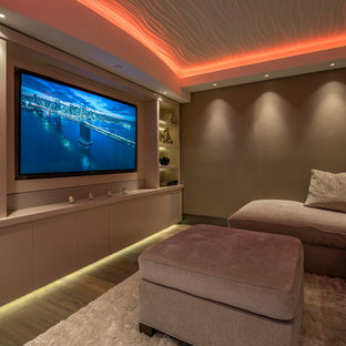 Photo of a contemporary home theatre in Miami with beige walls, medium hardwood floors and a built-in media wall.