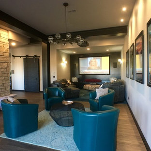 This is an example of a large contemporary open concept home theatre in Milwaukee with a wall-mounted tv, white walls, grey floor and vinyl floors.