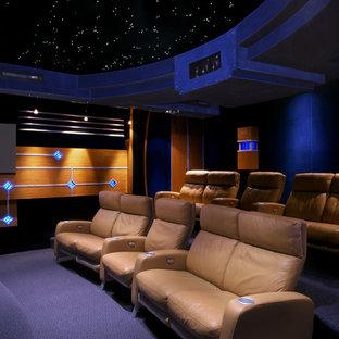 Foto de cine en casa cerrado, actual, extra grande, con paredes negras, moqueta, pantalla de proyección y suelo azul