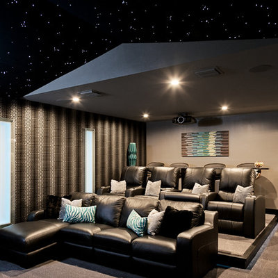 Inspiration for a large contemporary enclosed carpeted and beige floor home theater remodel in Orlando with a projector screen and gray walls