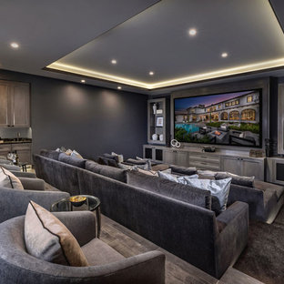 Mediterranean enclosed home theatre in Orange County with grey walls, carpet, a projector screen and brown floor.