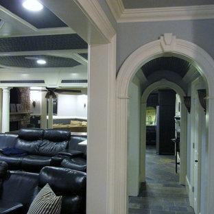 Immagine di un grande home theatre tradizionale chiuso con pareti grigie, pavimento in ardesia, pavimento grigio e TV a parete