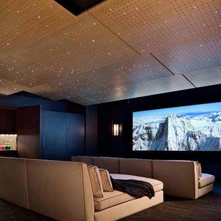Imagen de cine en casa cerrado, contemporáneo, de tamaño medio, con suelo marrón, paredes negras, moqueta y pantalla de proyección